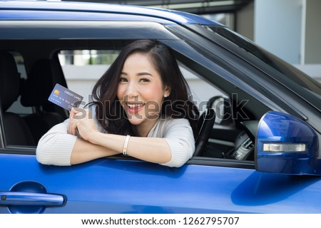 Happy beautiful Asian woman sitting inside new car blue and showing credit card pay for oil, pay a tire, maintenance on the garage, Make payment for refueling car on gas station, Automotive financing