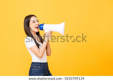Happy beautiful Asian woman talking on magaphone isolated on yellow background with copy space Stockfoto ©