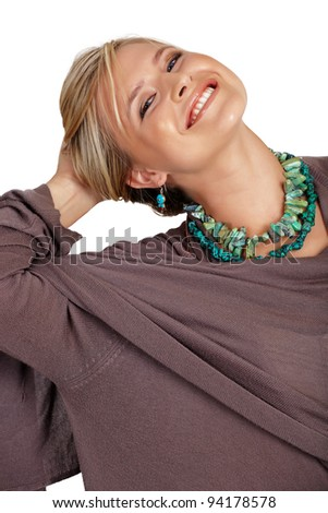 happy beautiful blond woman with blond hair wearing turquoise beads and a wrap on studio background