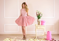 Happy Beautiful blonde girl in a pink dress. Baby doll delicate style. Soft portrait