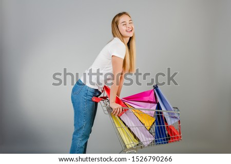 happy beautiful blonde woman has pushcart with colorful shopping bags isolated over grey