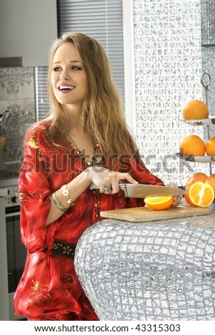 stock photo happy beautiful blonde woman in modern kitchen cuts oranges 43315303 Women Laughing at Sliced Oranges: Star of Trudeau keynote speech doesnt actually, uh, exist