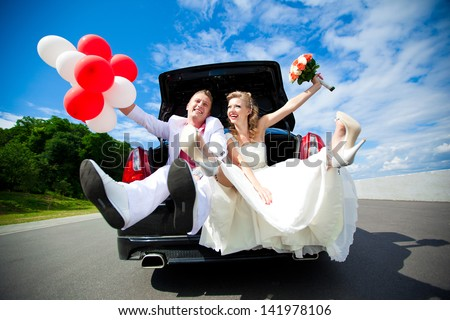 Happy beautiful bride and groom sitting in the trunk of a car. Honeymoon, fun and laughter.