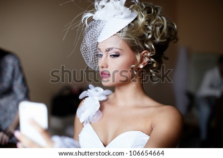 Happy beautiful bride blond girl in white wedding dress with hairstyle and bright makeup on home background looking in the mirror