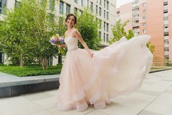 Happy beautiful bride outdoors. Pink wedding dress fluttering in the wind. Building in the background. Bouquet in hand