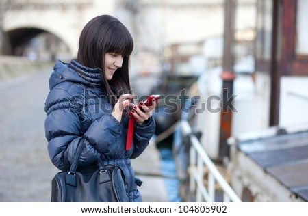 Happy beautiful brunette tourist in Paris sending an sms to a friend
