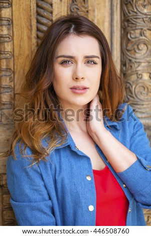 Happy Beautiful brunette woman on a background of wood doors