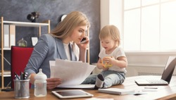 Happy beautiful business mom talking on smartphone and working with documents in office while her cute baby playing with toys. Business, motherhood, multitasking and family concept.