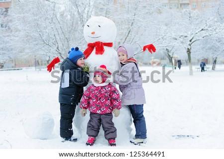 Happy beautiful children building snowman in garden