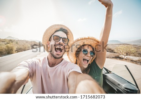 Happy beautiful couple in love taking a selfie portrait driving a convertible car on the road at vacation. Rental cars, holidays and people.