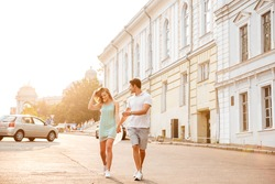 Happy beautiful couple walking on the city street in summertime
