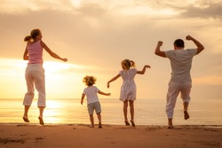 Happy beautiful family dancing on the  beach on the  dawn time.
