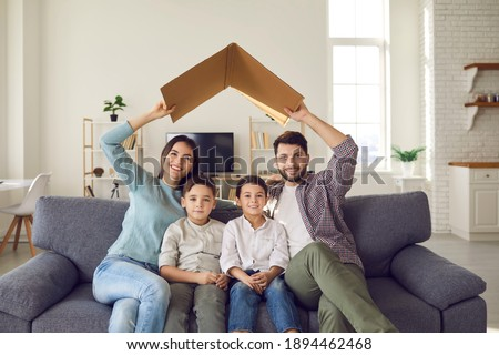 Happy beautiful family of four sitting on couch at home together. Smiling mommy and daddy holding symbolic roof above little kids on sofa. Mortgage, house insurance, future plans, protecting children