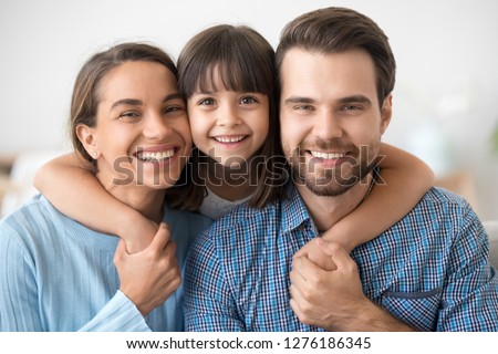 Happy beautiful family of three dad mom and little cute daughter portrait, child girl smiling embracing mother and father posing with parents looking at camera, kid hugging mommy daddy headshot