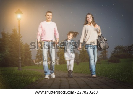 Happy beautiful family walking in a park - Mom and dad taking pretty daughter by hand
