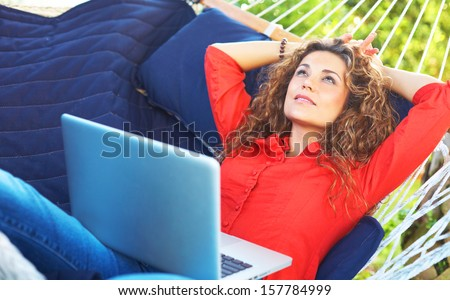 happy beautiful female laying in hammock typing on laptop looking up.Horizontal Image,young woman on vacation relaxing in hammock with lap top.
