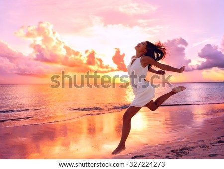 Happy beautiful free woman running on the beach at sunset jumping playful having fun in serene picturesque sunset at the ocean . Aspirational happy lifestyle with pretty young lady enjoying freedom.