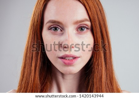 happy beautiful ginger hair ,green eyes caucasian woman with perfect skin and charming snow-white smile , looking winking at the camera passport frontal photo white studio background.