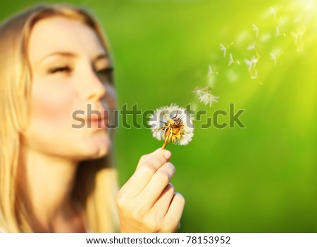 Happy beautiful girl blowing dandelion, over green nature background, selective focus, wish concept