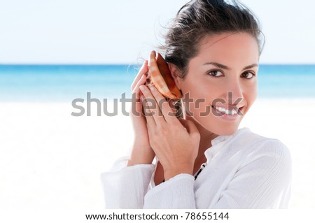 Happy beautiful girl holding and hearing a shell in a tropical beach