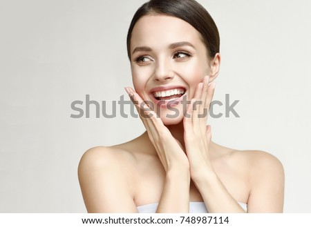 Photo of Happy beautiful girl holding her cheeks with a laugh   looking to the side. Pretty woman   clean fresh skin . Expressive facial expressions  .Cosmetology , beauty and Spa