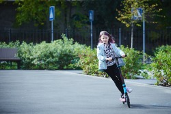 Happy beautiful girl is riding along the street on the kick scooter on a windy day. Baby having free time playing. The concept of a healthy lifestyle. Kids sport
