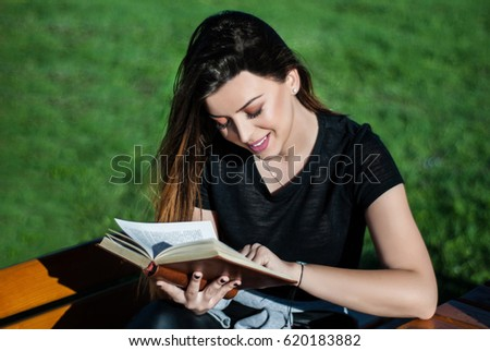 Happy beautiful girl reading a book on sunny spring day on a bench in nature Foto stock ©