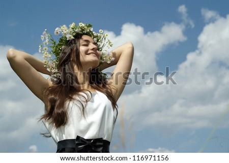 happy beautiful girl standing against the sky