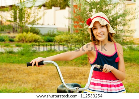 Happy beautiful girl with her bicycle near home on sunset half-length portrait