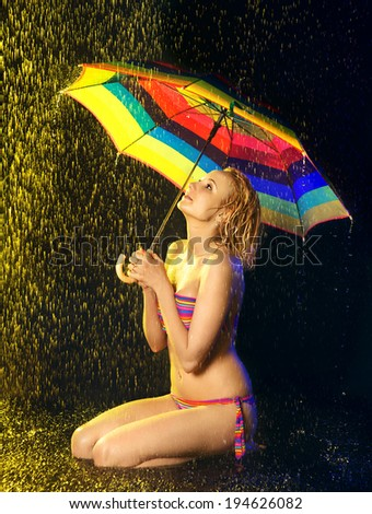 happy beautiful girl with umbrella under rain, black background