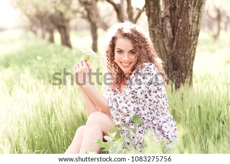 Happy beautiful girl 20-24 year old holding flowers outdoors. Looking at camera. 20s.  #1083275756