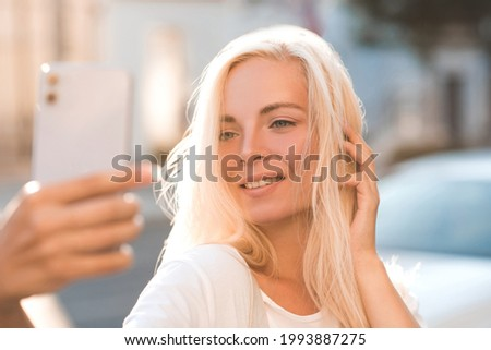 Happy beautiful girl 20-24 year old making selfie with phone over city background closeup. Looking at telephone have video call with friends. Happiness.  Foto stock ©