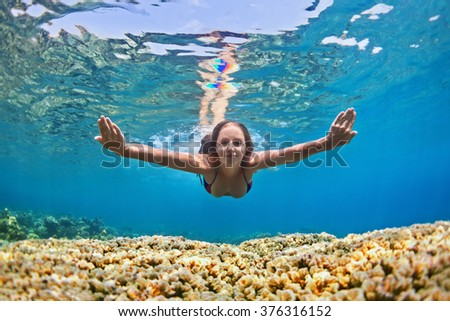 Happy beautiful girl - young woman dive underwater with fun over coral reef in sea pool. Healthy active lifestyle, people water sport outdoor activity and swimming lessons on beach summer holidays.