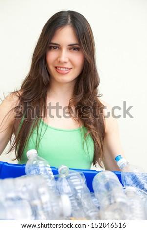 Happy beautiful hispanic female holding recycling bin