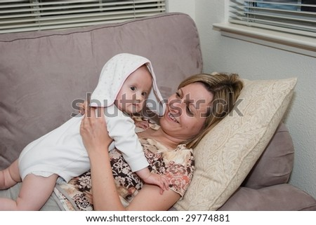 Happy beautiful laughing mother lies on the sofa with her baby