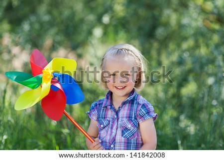Happy beautiful little blond girl with a large pinwheel or toy windmill in the colours of the rainbow standing outdoors against greenery