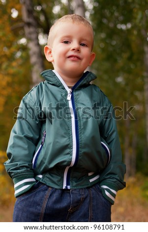Happy beautiful little boy outdoor in autumn