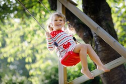 Happy beautiful little toddler girl having fun on swing in domestic garden. Cute healthy child swinging under blooming trees on sunny spring day. Baby laughing and crying