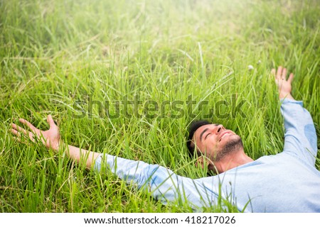 Happy beautiful man lying on the green grass with arms outstretched