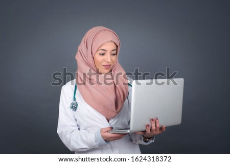Happy beautiful muslim doctor woman wearing medical uniform, working with her laptop and having stunned expression.