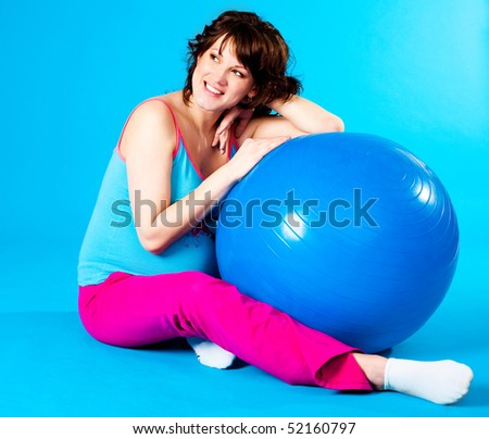 happy beautiful pregnant woman making some exercises on a fitness ball