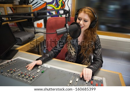 Happy beautiful radio host moderating sitting in studio at college