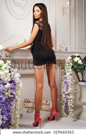 happy, beautiful, slender, swarthy, tall brunette girl with model looks in a little black dress with long, straight, beautiful, healthy, shiny hair, brown eyes and sparkling white smile in interior #329660363