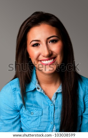 Happy beautiful smiling female student portrait of face with long hair on gray.