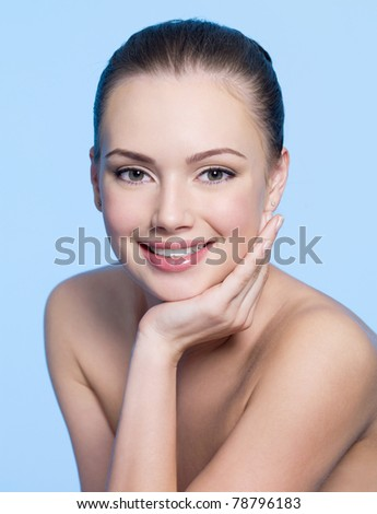 Happy beautiful teen girl face with clean healthy skin - blue background