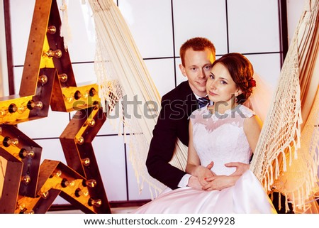 Happy beautiful wedding couple is embracing swinging in hammock at window with yellow star background.