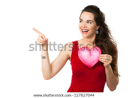 Happy beautiful woman holding a love heart and pointing at copy-space. Isolated on white.