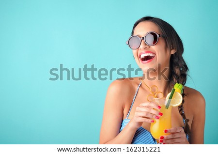 Happy Beautiful Woman Holding A Tropical Cocktail With Sunglasses On Bright Background