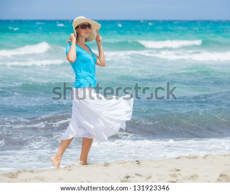 Happy beautiful woman in the beach hat looking at the sea