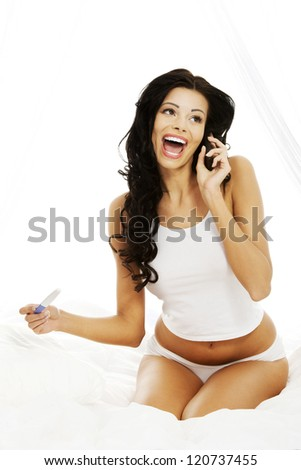 Happy beautiful woman on bed with pregnancy test in hand calling to somebody